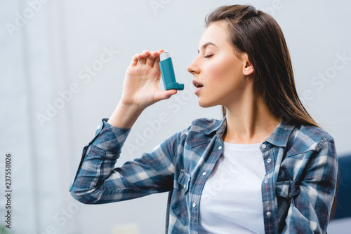 young woman using inhaler while suffering from asthma at home Wallpaper Mural
