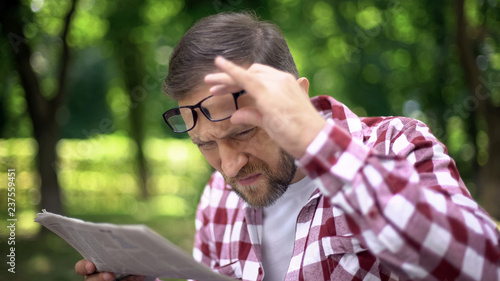 Fotografía Male trying to read newspaper in park, poor sight, farsightedness, myopia