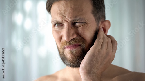 Photographie  Sick guy feeling ear pain, health care, neurological infection, itchiness otitis