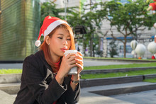 Asian Woman Drinking Coffee Wandering In The Grass Of Madrid In Winter,and Celebrate Christmas Alone,