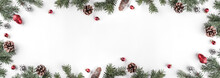 Creative Frame Made Of Christmas Fir Branches On White Background With Red Decoration, Pine Cones. Xmas And New Year Theme. Flat Lay, Top View, Wide Composition