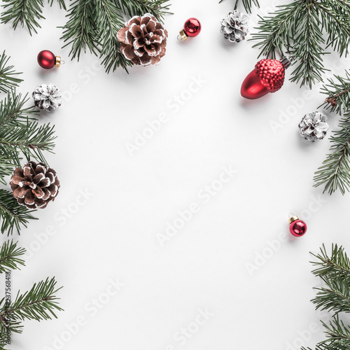 Creative frame made of Christmas fir branches on white paper background with red decoration, pine cones. Xmas and New Year theme. Flat lay, top view