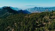 aerial drone footage of beautiful stunning landscape view off the Roque Nublo track at Gran Canaria Spain with a valleys and many small peaks with Tenerife island at the background above the clouds