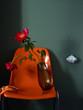 Blumen Stillife auf orangem Stuhl vor grüner Wand