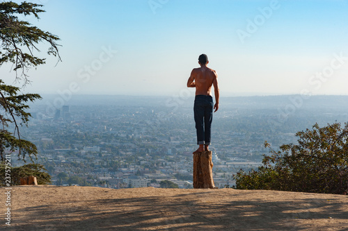 Photo Man standing on a dead tree stump in Griffith park looking out over the city of