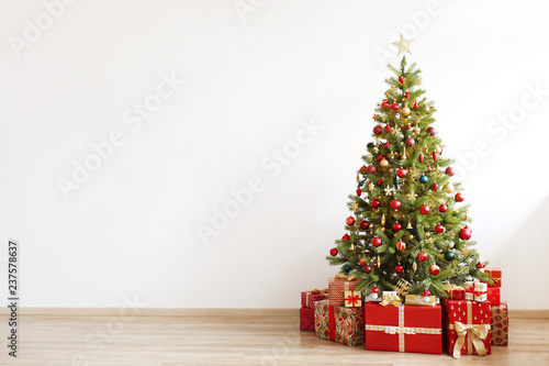 Foto op Canvas Kerstmis Big beautiful christmas tree decorated with beautiful shiny baubles and many different presents on wooden floor. White wall background with a lot of copy space for text. Close up.