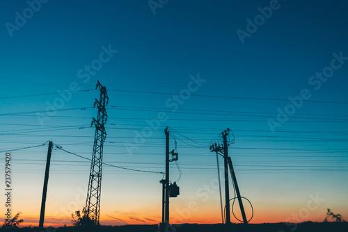 Power lines in field on sunrise background Fototapeta