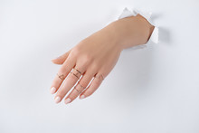Cropped Image Of Woman Holding Hand With Beautiful Luxury Silver Rings Through White Paper