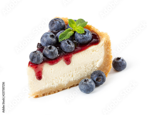 Piece of cheesecake with blueberries and mint isolated on white