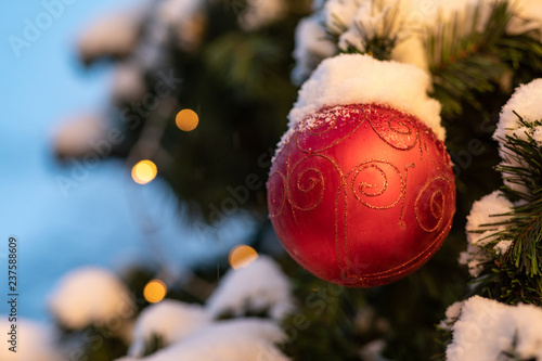 Foto  Red ball with a golden star on a snow-covered fir tree