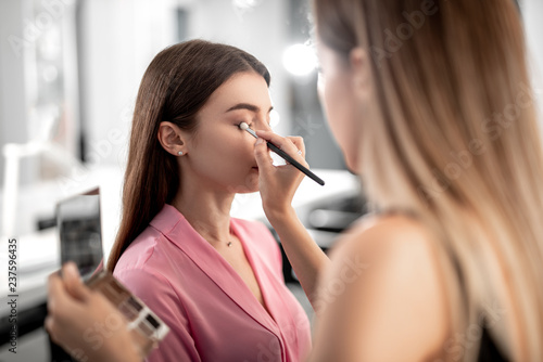 Staande foto Hoogte schaal Visagiste holding palette with shadows while making make-up for pretty lady with special brush