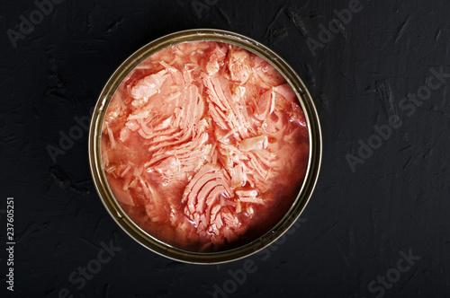 Fotografía  Tin with tuna slices on a black background