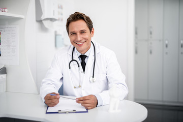 Fototapeta Happy doctor. Positive enthusiastic general practitioner sitting at the table in his clinic and smiling while holding a pen