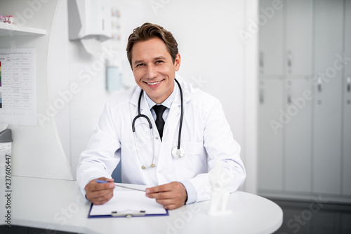 Staande foto Hoogte schaal Happy doctor. Positive enthusiastic general practitioner sitting at the table in his clinic and smiling while holding a pen