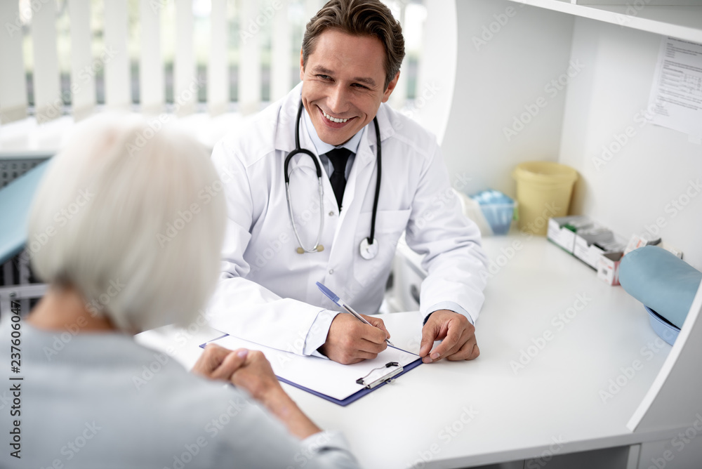 Fototapeta Positive emotional general practitioner sitting with the clipboard on the table and kindly smiling to his patient