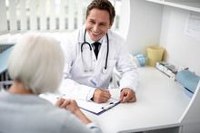Positive Emotional General Practitioner Sitting With The Clipboard On The Table And Kindly Smiling To His Patient