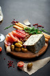 Mediterranean products (ham, blue cheese, arugula, cherry, nuts) on a brown cutting board. Dark background. Useful natural fresh food. Place for text