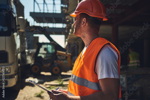 Fotografía  Professional builder in orange uniform standing outdoors with clipboard in his h