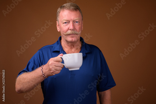 Photo  Handsome senior man with mustache holding coffee cup