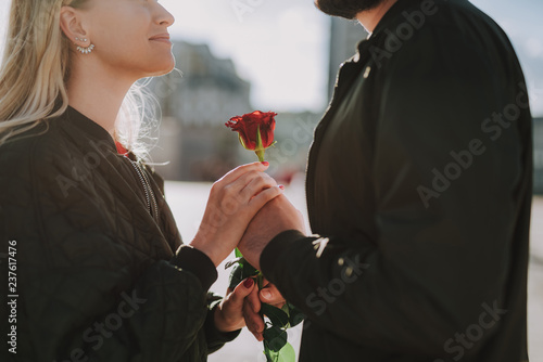 Gift for you. Cropped close up portrait of young man giving beautiful flower to his girlfriend while she smiling
