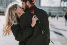 Waist Up Portrait Of Charming Lady Holding Red Rose And Sharing Romantic Moment With Her Boyfriend