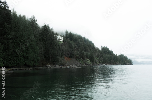 Photo  On a moody PNW day, one can see a beautiful cliff side home overlooking a green