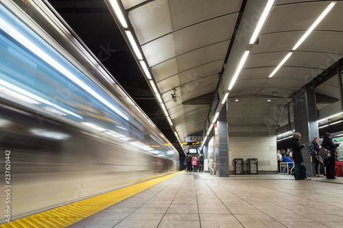 Vancouver City Center station at evening rush hour with trains rushing by and
