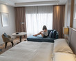 A woman sits on a couch in a minimally decorated clean high end luxury hotel room