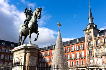 Madrid - Plaza Mayor, bronze statue of King Philip III, Christmas tree and painting facade.