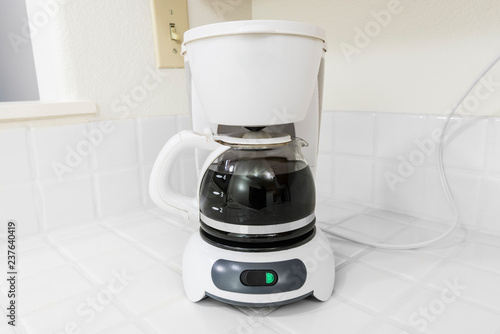 Canvas-taulu Small white coffee maker on clean white tile kitchen counter.
