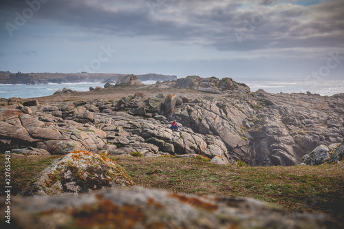 Fotografia  young woman sitting on rocks  of the island of Yeu