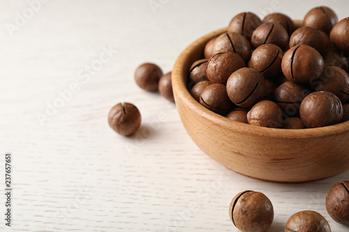 Bowl with organic Macadamia nuts on white table