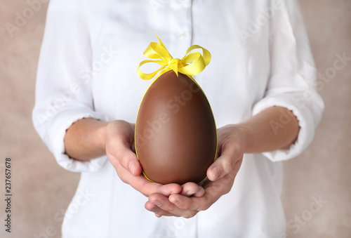 Woman holding chocolate Easter egg with bow knot on color background, closeup