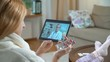 Medicine online. Young woman consultations with her doctor using video chat at home. The doctor showing her the results of medical tests