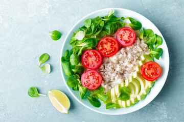 Fototapeta Oatmeal porridge with avocado and vegetable salad of fresh tomatoes and lettuce. Healthy dietary breakfast. Top view