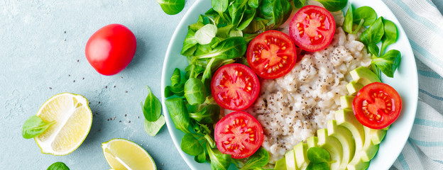 Fototapeta Oatmeal porridge with avocado and vegetable salad of fresh tomatoes and lettuce. Healthy dietary breakfast. Top view. Banner