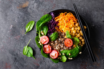 Fototapeta Healthy vegetarian dish with buckwheat and vegetable salad of chickpea, kale, carrot, fresh tomatoes, spinach leaves and pine nuts. Buddha bowl. Balanced food. Delicious detox diet.Top view
