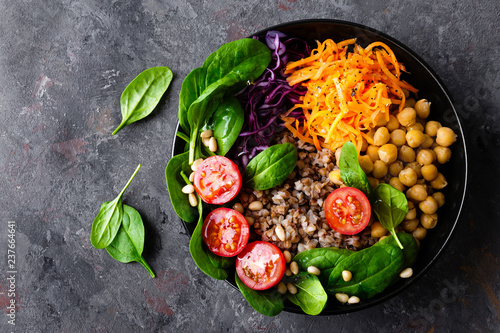 Spoed Fotobehang Klaar gerecht Healthy vegetarian dish with buckwheat and vegetable salad of chickpea, kale, carrot, fresh tomatoes, spinach leaves and pine nuts. Buddha bowl. Balanced food. Delicious detox diet.Top view