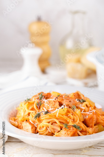 Spaghetti bolognese pasta with tomato sauce, vegetables and chicken meat on white wooden rustic background. Traditional italian food