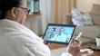 Medicine online. Elderly woman is consulting with male doctor using video chat at home. The doctor prescribing her a nosal medicine for a cold.
