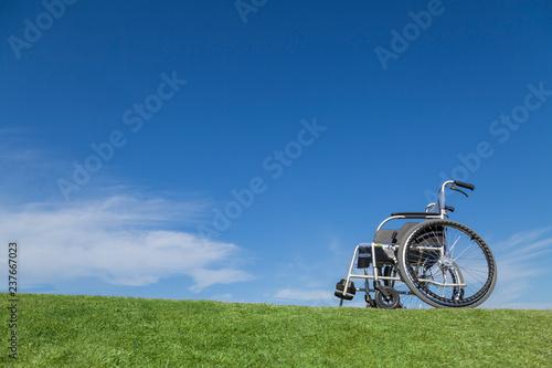 青空バックを背景に芝の上に置かれた無人の車イス。福祉、介護、病気、障害者、老後イメージ Fototapeta
