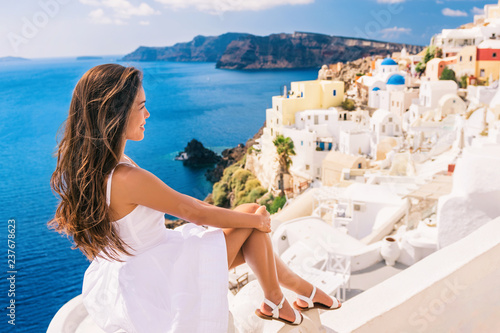 Fototapeta Europe summer travel destination Santorini tourist woman on vacation relaxing. Asian girl in white dress looking at famous white village Oia with the mediterranean sea and blue domes. obraz