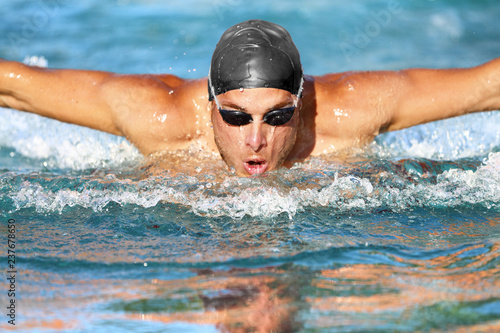 Swimmer. Man swimming butterfly strokes in pool competition. Competitive male sport athlete swimmer wearing swimming goggles and cap. Young caucasian fitness model face portrait.