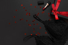 Black Gift Box With Red Ribbon, Lace Bra Underwear, Red Lipstick, Holographic Confetti On Dark Background Top View Flat Lay. Female Essential Erotic Accessories, Fashionable Underwear, Gift To Woman