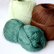 Three skeins for knitting brown, dark green and light green.