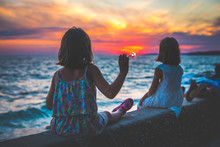 Twin Girls Sisters Are Watching Amazing Sea Sunset In Croatia.