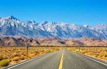 Empty Road Near Lone Pine With Rocks Of The Alabama Hills And The Sierra Nevada In The Background, Inyo County, California, United States.