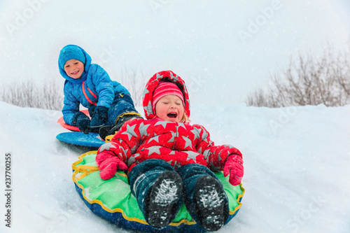 little boy and girl sliding in winter snow