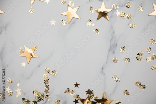 Fototapeta Gold star sparkle party confetti on a marble flat lay background obraz na płótnie