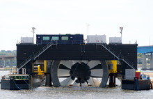 Giant Tidal Turbine Docked In A Harbor. It Is Held In A Ship Designed To Hold And Transport It. Sky Is Overcast. Walkways On Ship Give Sense Of Scale. Identifying Marks Removed. Room For Text.